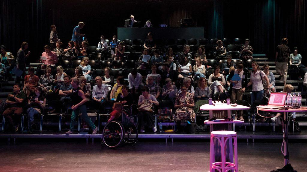 2018 ALL IN Symposium in Köln. Viele Menschen sitzen im Theater und warten bis das Symposium los geht. Der Raum ist dunkel.