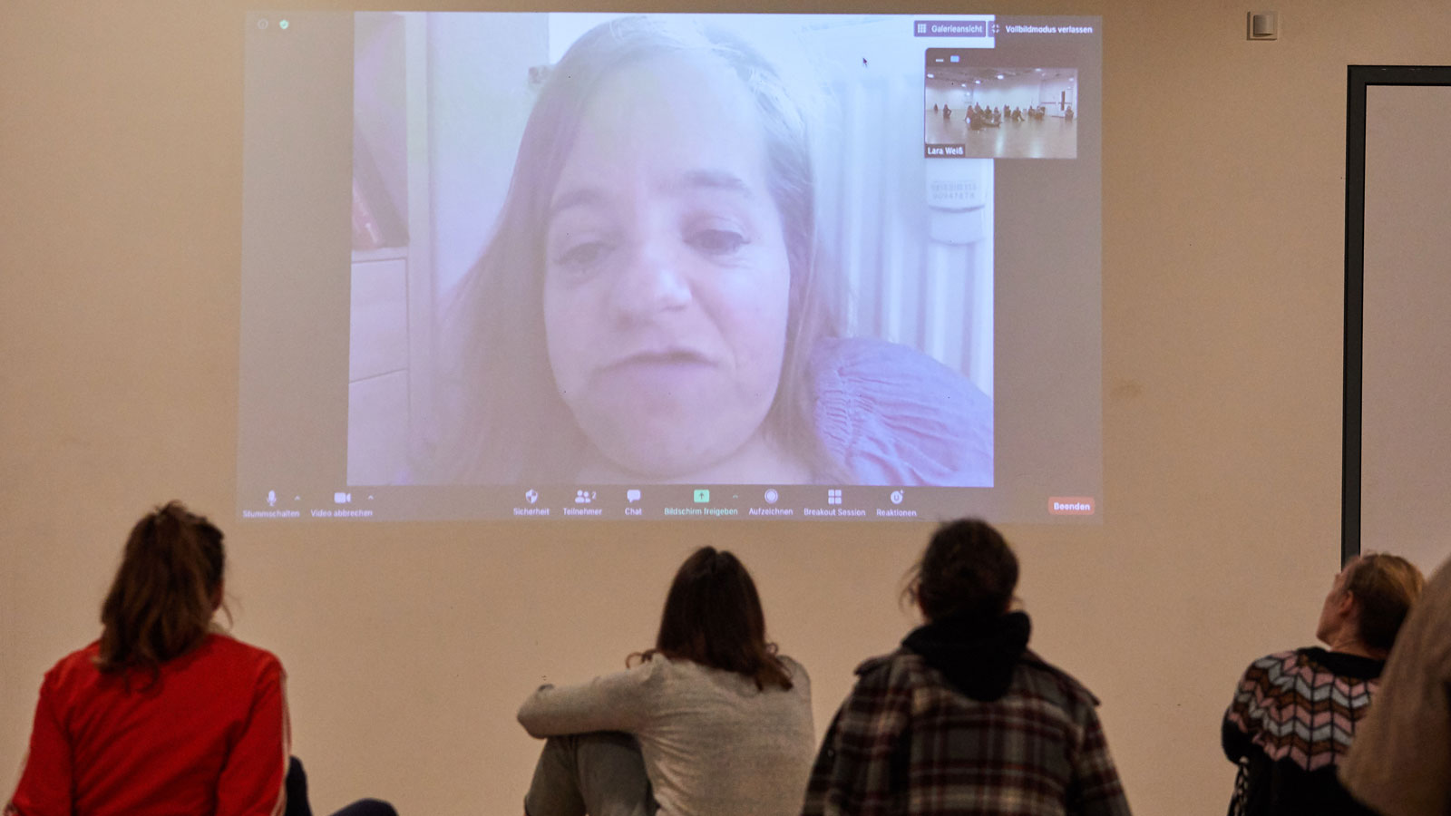 At the ALL IN Symposium. Jana Zöll is present at the workshop via Zoom. Her picture is projected onto the wall. The participants sit in front of it. ©Anna Spindelndreier