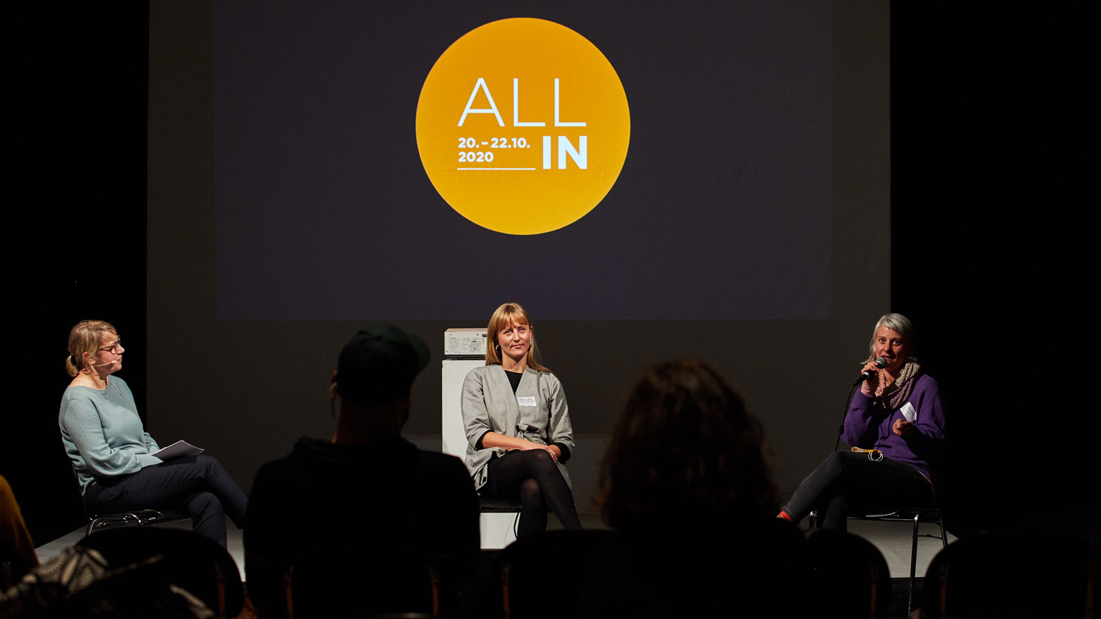 At the ALL IN Symposium. Three women sit in a semicircle on the stage. Behind them you can see the ALL IN logo. An orange circle with the text ALL IN 20 - 22.10.2020. ©Anna Spindelndreier