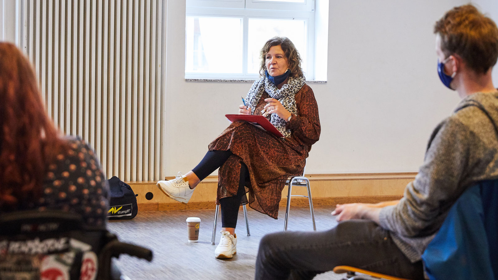 At the ALL IN Symposium. Bettina Masuch is sitting on a chair. She talks to people who are participating in her workshop. ©Anna Spindelndreier