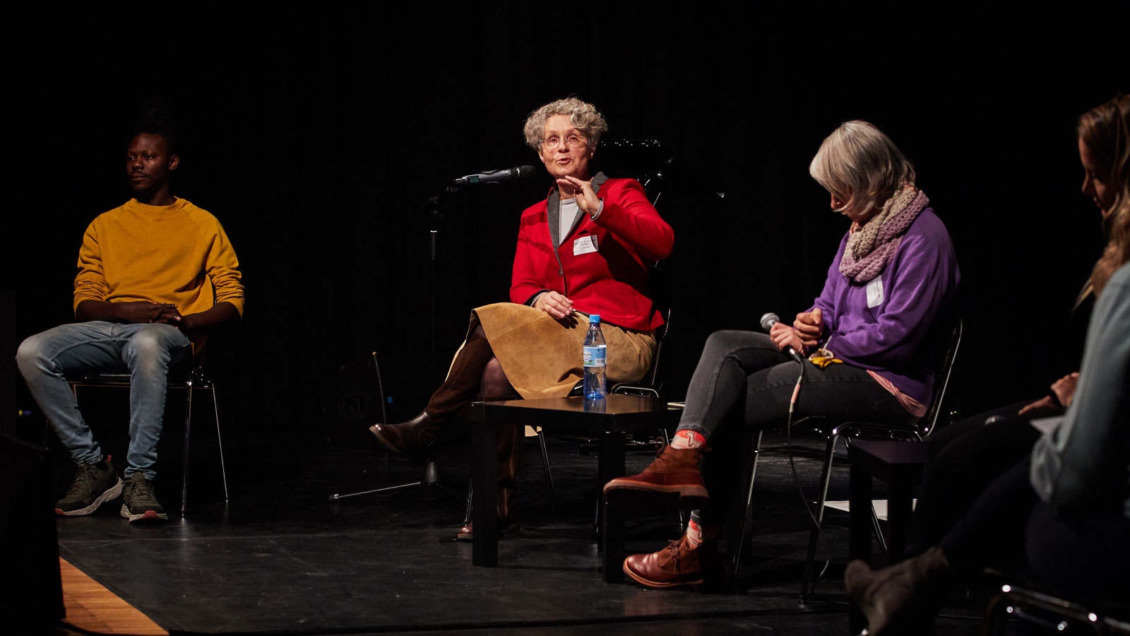 At the ALL IN Symposium. Dodzi Dougban, Dr. Susanne Quinten and Miriam Michel are sitting on the stage in a semicircle. ©Anna Spindelndreier