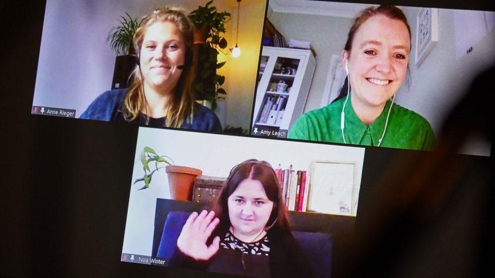 Beim ALL IN Symposium. Anne Rieger, Noa Winter und Amy Leach sind über Zoom dabei. Das Video wird auf die Bühne projiziert. ©Anna Spindelndreier