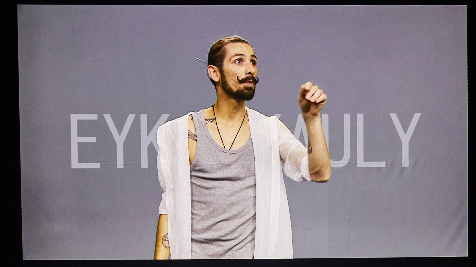 At the ALL IN Symposium. Eyk Kauly's performance. His video is projected onto the stage. ©Anna Spindelndreier