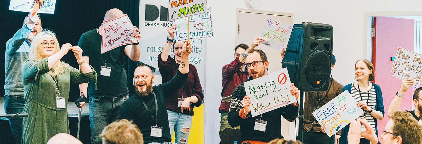 Die Drake Music Company - viele Menschen halten Schilder hoch