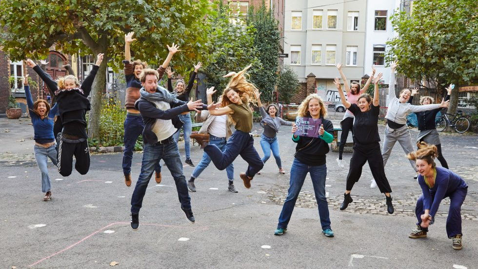 Many people jump into the air. In the middle is Lisette Reuter with the award from The Power of the Arts. ©Anna Spindelndreier