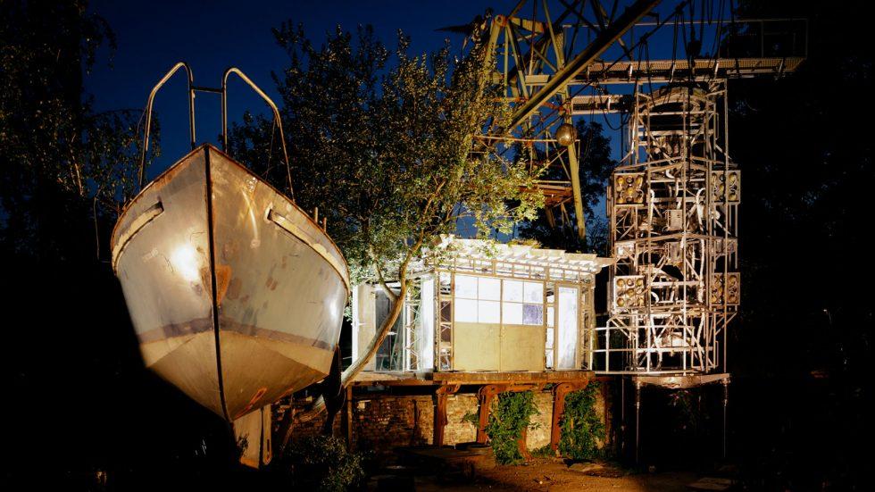 Links ein Schiff von vorne, erstrahlt in goldenem Licht. Daneben eine hell erleuchtete Hütte. Dahinter ein raketenförmiger Mast. Es ist Nacht. Zwischen dem Schiff und dem Haus steht ein Baum. RoboLAB 2020 © Jörn Neumann